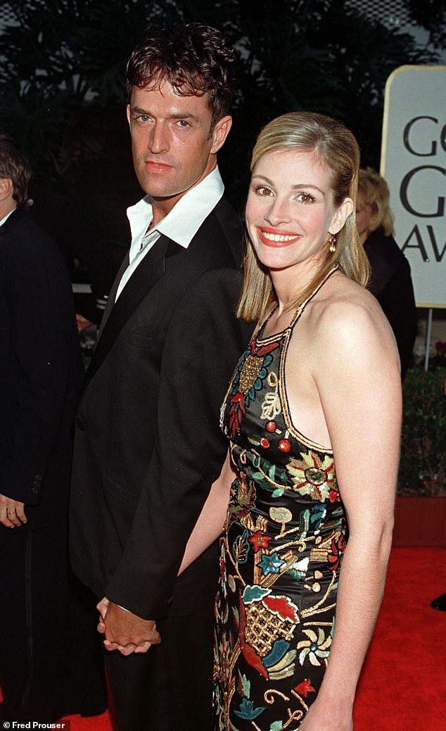Everett with Julia Roberts at The Golden Globes in 1998. 'For all my fantasy about being fabulous in front of paparazzi and being amusing like David Niven and Roger Moore on chat shows, I couldn't do it. I was too shy'